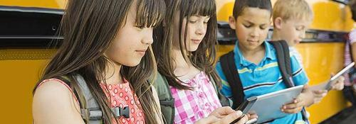 K-12 students waiting by bus using tablets and mobile phones.