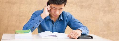 College student studying using mobile phone and textbook