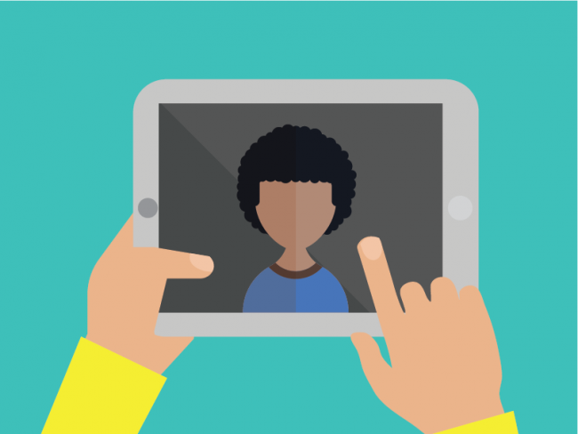 Hands holding a tablet with image of person in screen.