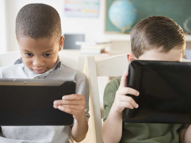 Two young boys using tablets for classwork.