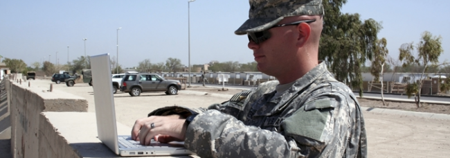 Soldier outside at base using his laptop computer