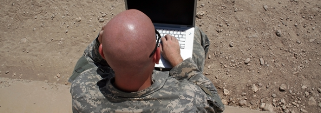 Overhead view of soldier using laptop outside