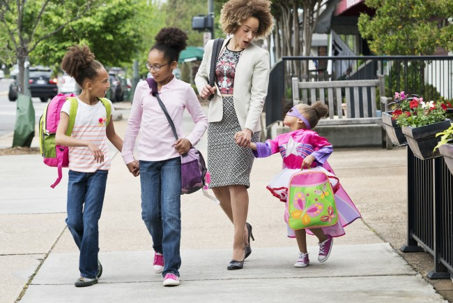 Mom walking daughters to school