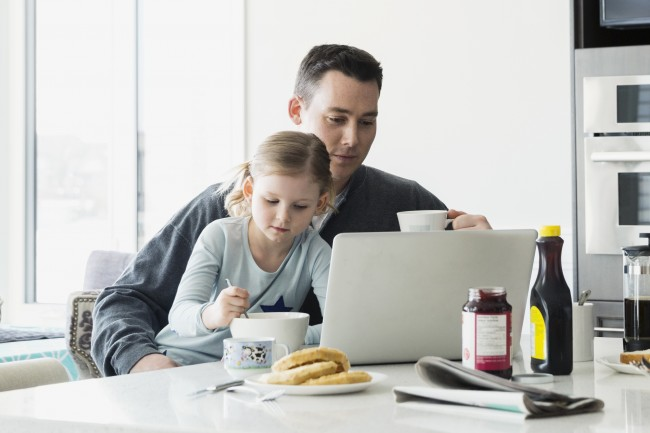 Father looking at computer while daughter sits on his lap