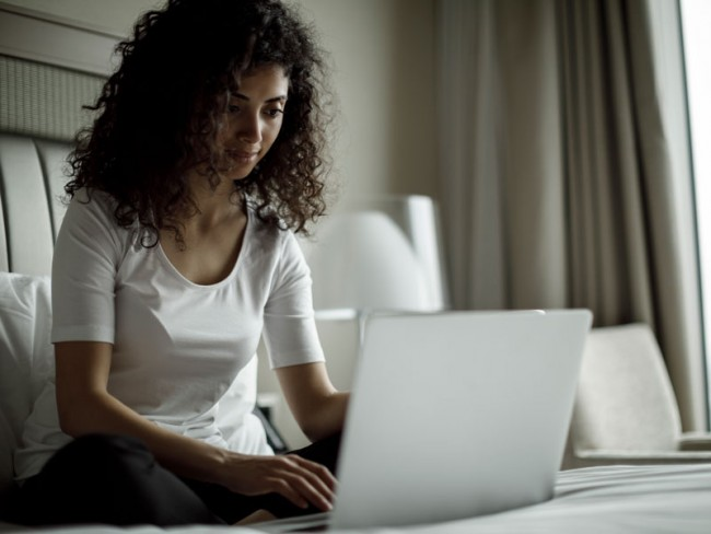 Young adult woman using a computer on her bed