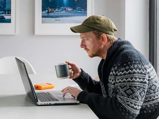 Man at kitchen table drinking coffee and taking an online course from home