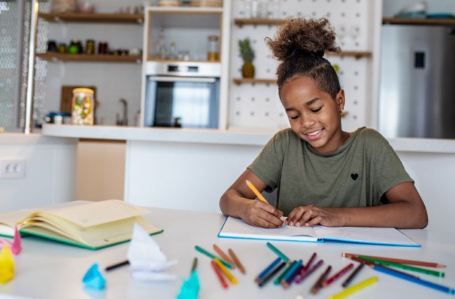 Young student works on school work from kitchen table